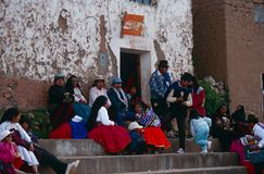 Colourfully attired people in Peru. Colourfully-attired people in Peru sat outside a shop Stock Photo