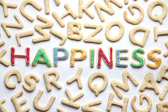 Colourfully decorated letter shaped cookies HAPPINESS amongst plain ones. Colourfully decorated letter shaped cookies arranged to spel HAPPINESS amongst plain Stock Photo