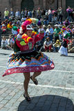 A colourfully dressed lady performs down a Cusco street during the May Day parade in  Peru. A colourfully dressed Peruvian lady dances past the Cathedral of Royalty Free Stock Photos