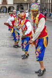 Colourfully dressed men perform down a Cusco street during the May Day parade in Peru. Colourfully dressed Peruvian men dance at the Plaza de Armas in Cusco in Royalty Free Stock Image