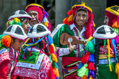Colourfully dressed performers in a Cusco street during the May Day parade in  Peru. Colourfully dressed performers pose for a photograph at Plaza de Armas in Royalty Free Stock Image