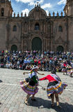 Colourfully dressed performers dance down a Cusco street during the May Day parade in  Peru. Colourfully dressed performers dance in front of the Cathedral of Royalty Free Stock Photos