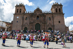 Colourfully dressed performers dance down a Cusco street during the May Day parade in  Peru. Colourfully dressed performers dance past the Cathedral of Cusco at Royalty Free Stock Photography