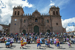 Colourfully dressed performers dance down a Cusco street during the May Day parade in  Peru. Colourfully dressed performers dance past the Cathedral of Cusco at Royalty Free Stock Photo