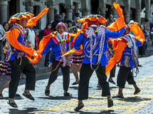 Colourfully dressed performers dance down a Cusco street during the May Day parade in  Peru. Colourfully dressed performers dance at Plaza de Armas in Cusco Stock Photo