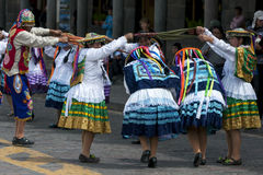 Colourfully dressed performers dance down a Cusco street during the May Day parade in  Peru. Colourfully dressed performers dance at the Plaza de Armas in Cusco Stock Photo