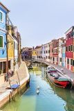 Colourfully painted houses and canal with boats on Burano island,Italy. Colored houses in Burano -an island in the Venetian Lagoon Stock Image