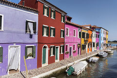 Colourfully painted houses and canal with boats on Burano island,Italy. Colored houses in Burano -an island in the Venetian Lagoon Royalty Free Stock Images