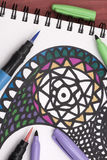Colouring a mandala. A vertical overhead view of the colouring of a mandala with some of the markers needed Royalty Free Stock Images