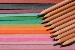 Colouring pencils on a multicoloured paper background royalty free stock photos