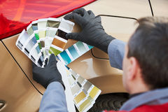 Colourist man selecting color of car with paint matching samples. Auto colour matching. colourist man selecting color of car at automobile repair and renew stock photo