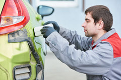 Colourist man selecting color of car with paint matching scanner Royalty Free Stock Photography
