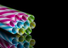0588 Colourly striped plastic drinking straws bundled, black mirroring underground background. Colourly striped plastic drinking straws bundled, black mirroring stock photo