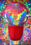 Colours. Ball of glass on a vase, magenta tinted liquid and multi-coloured background stock images