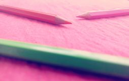 Colours. Beautiful pencil colours pink orange green kept on red cotton cloth Royalty Free Stock Images
