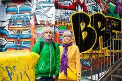 Colours everywhere. Colourfoul couple near graffiti wall Stock Photography