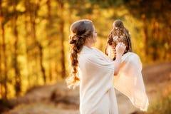 Colpi della ragazza un falco che si siede sulla sua mano nei raggi del tramonto immagine stock libera da diritti