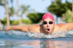 Colpi di farfalla di nuoto dell'uomo del nuotatore in stagno Fotografia Stock