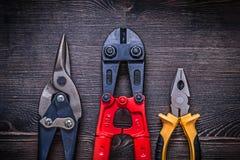 Colpi di forbici d'acciaio della latta della taglierina delle pinze sul bordo di legno Fotografia Stock