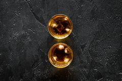 Colpi di whiskey con ghiaccio su derisione nera di vista superiore del fondo della tavola della barra su Fotografia Stock Libera da Diritti