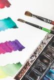 Colpi variopinti dell'acquerello in album, pitture e pennelli del disegno Fotografia Stock