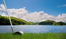 Colpire la sfera di golf sopra il lago Fotografia Stock
