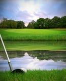 Colpire la sfera di golf sopra il rischio dell'acqua fotografia stock libera da diritti