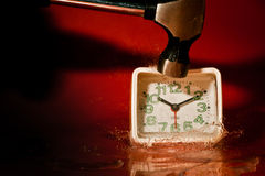 Colpire un orologio con un martello fotografie stock