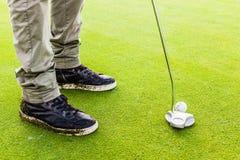 Colpire una palla da golf con un club del putter Fotografie Stock