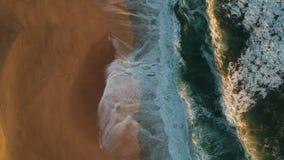 Colpo aereo che vola indietro sopra le onde sulla spiaggia sabbiosa vuota nel Portogallo archivi video