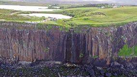 Colpo aereo cinematografico della linea costiera drammatica alle scogliere vicino alla cascata famosa della roccia del kilt, Skye archivi video