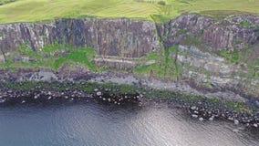Colpo aereo cinematografico della linea costiera drammatica alle scogliere vicino alla cascata famosa della roccia del kilt, Skye video d archivio