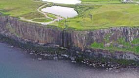 Colpo aereo cinematografico della linea costiera drammatica alle scogliere vicino alla cascata famosa della roccia del kilt, Skye stock footage