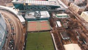 Colpo aereo degli atleti che giocano a calcio sul campo di erba verde all'area della città stock footage