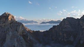 Colpo aereo dei picchi di montagna di Caucaso sopra le nuvole al tramonto Nebbia nella valle della montagna stock footage