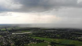 Colpo aereo del fuco di piovosità pesante che si avvicina al villaggio suburbano video d archivio