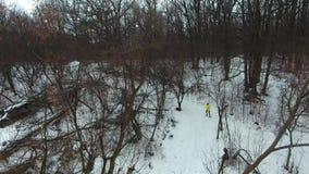 Colpo aereo del pareggiatore maschio in cappotto giallo che esegue sulla collina nella foresta di inverno stock footage