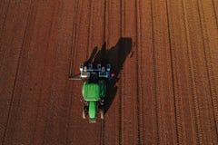 Colpo aereo dell'agricoltore con un trattore sul campo agricolo Immagine Stock Libera da Diritti