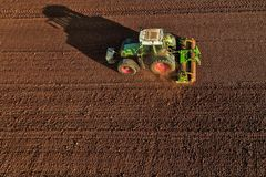 Colpo aereo dell'agricoltore con un trattore sul campo agricolo Fotografia Stock Libera da Diritti