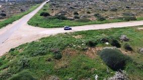 Colpo aereo dell'automobile bianca che si avvicina sulla strada campestre, spiaggia Mediterranea archivi video
