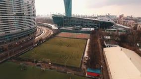Colpo aereo della gente che gioca a calcio sul campo di erba verde all'area della città stock footage