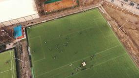 Colpo aereo della gente che gioca a calcio sul campo di erba verde il giorno di estate stock footage