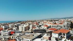 Colpo aereo della pentola 360 della città di paphos con le automobili, i parcheggi e le costruzioni con le montagne arancio rosse video d archivio
