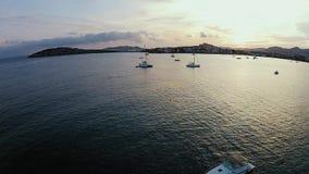 Colpo aereo delle barche e degli yacht vicino alla riva di Ibiza, tramonto archivi video
