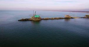 Colpo aereo delle case di alcuni pescatori con l'esterno enorme delle reti situato in mezzo al mare, in Toscana, l'Italia archivi video