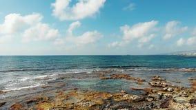 Colpo aereo delle onde di oceano che colpiscono spiaggia rocciosa Cielo blu con le nuvole bianche sull'orizzonte Giorno ventoso s stock footage