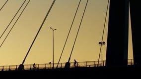 Colpo aereo delle siluette dei ciclisti sul ponte guyed Fotografia Stock Libera da Diritti