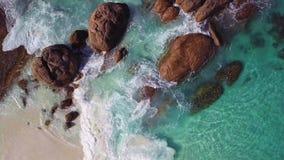 Colpo aereo di belle rocce su una spiaggia con le onde che turbinano intorno loro archivi video