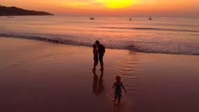 Colpo aereo di giovane coppia che bacia durante il tramonto con il loro figlio che corre vicino archivi video