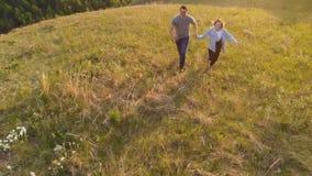 Colpo aereo di giovane coppia che corre felicemente attraverso un prato della montagna al tramonto archivi video